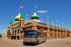 A brown bus parked in front of the Corn Palace.